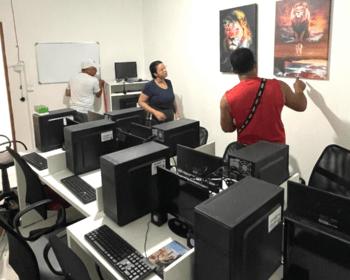 dois homens e uma mulher preparam últimos detalhes do laboratório de informática montado para oferecer os cursos